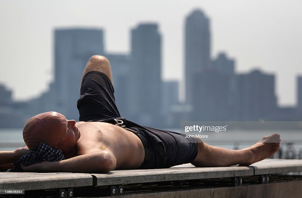 A sunbather lies out in Westside Park with a view of the Jersey City skyline on June 21, 2012 in New York City. City residents enjoyed - or endured a second day of the summer's first heat wave, with temperatures reaching the mid 90's.