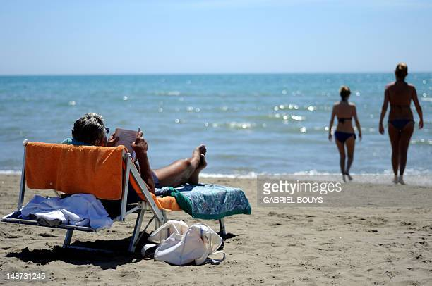 A sunbather reads on a private beach in Fiumicino near Rome on July 18 2012 A law established in 2006 guarantees free public access to the country's...