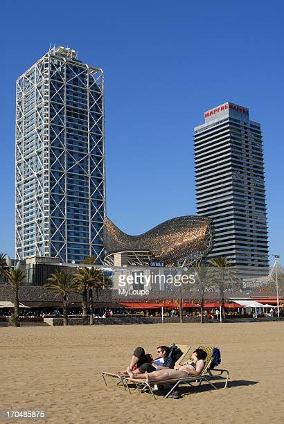 Sunbathers at Barceloneta Beach with Frank Gehry's Fish Sculpture Mapfre Tower Building and Arts Hotel Barcelona Catalonia Spain