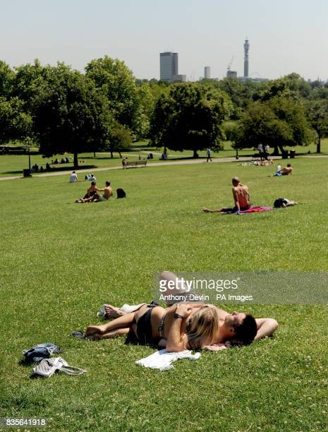 Sunbathers enjoy the sunshine on Primrose Hill London