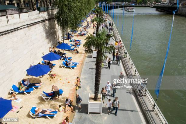 Sunbathers on banks of River Siene at the Paris Plage (Paris beach).