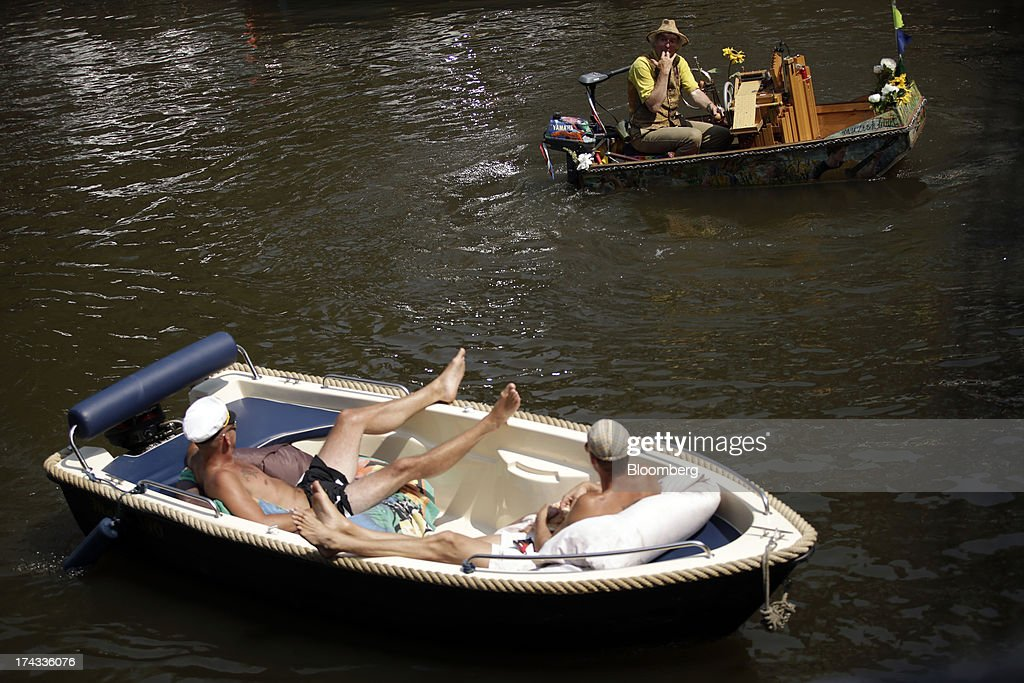 Sunbathers sit and watch boats sail past them on a canal in Amsterdam, Netherlands, on Tuesday, July 23, 2013. Dutch pension funds will be allowed to calculate liabilities on the basis of an adjusted discount rate as the government seeks to keep the retirement system viable amid low interest rates and an aging population. Photographer: Matthew Lloyd/Bloomberg via Getty Images