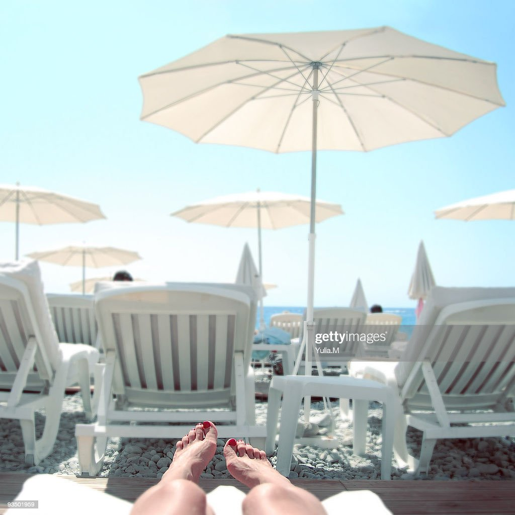 Sunbathing looking out to sea : Stock Photo