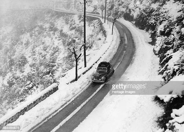 A Sunbeam MKII during the Monte Carlo Rally 1956 Sunbeam on a stretch of curving road in a snowy landscape