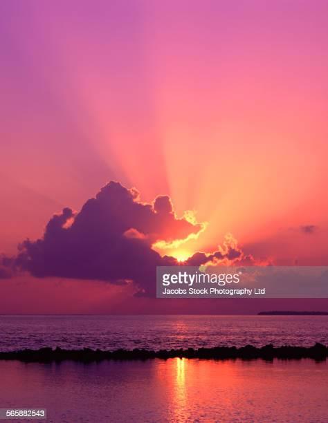 Sunbeams behind clouds in vivid sunset sky reflecting in ocean water