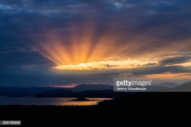 Sunbeams in cloudy sky over remote lake