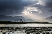 Sunbeams in stormy sky over lake, Scotland