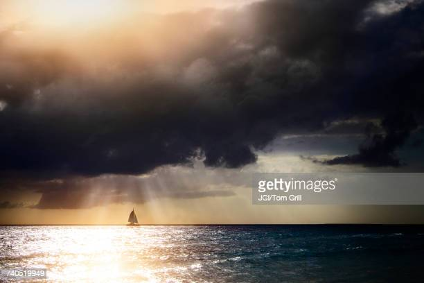 Sunbeams through storm clouds over sailboat