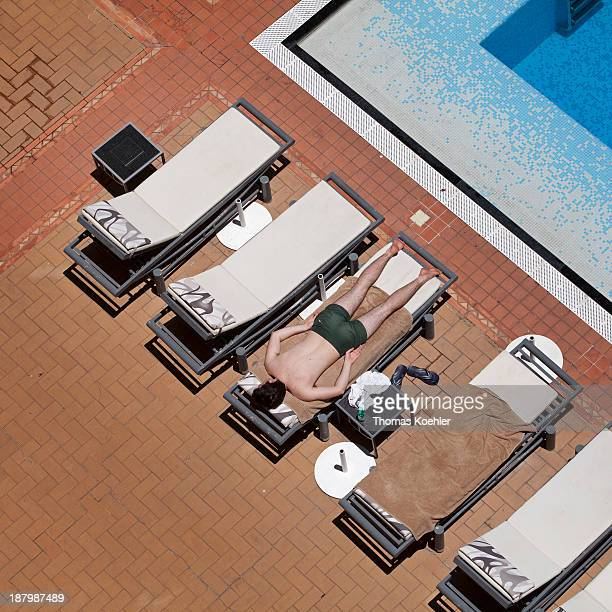 Sunbeds at a pool man sunbathing at a hotel pool