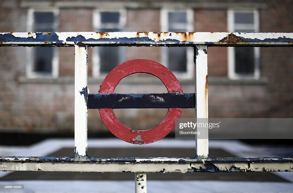 A sun-bleached London Underground logo sits on a rusty gate outside a closed Redbridge subway station in London, U.K., on Wednesday, Feb. 5, 2014. A two-day strike by London Underground employees over job cuts and closures began last night, threatening the capital with travel chaos. Photographer: Chris Ratcliffe/Bloomberg via Getty Images