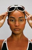 Hispanic woman with sunglass sunburn outline on face