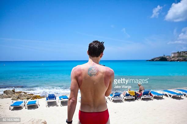 Sunburned and tattooed man on beach using smart phone