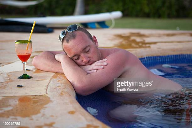 Sunburned man asleep with drink in hot tub.