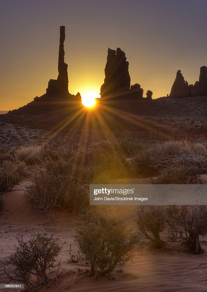 A sunburst through the famous Totem Pole formation in Monument Valley, Utah.