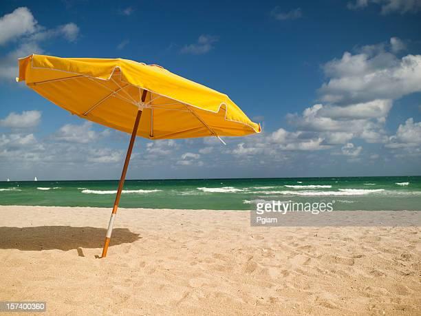 Liegestühlen und Sonnenschirm am Strand