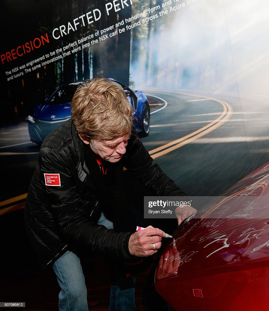 Sundance Institute President and Founder Robert Redford autographs the hood of a 2017 Acura NSX during the 2016 Sundance Film Festival on January 26...
