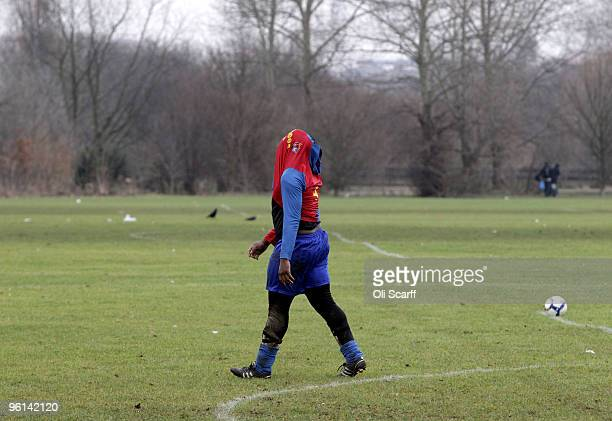 Sunday League footballer for 'The Cock Tavern' covers his head with his shirt after missing a penalty during a match on the Hackney Marshes' pitches...