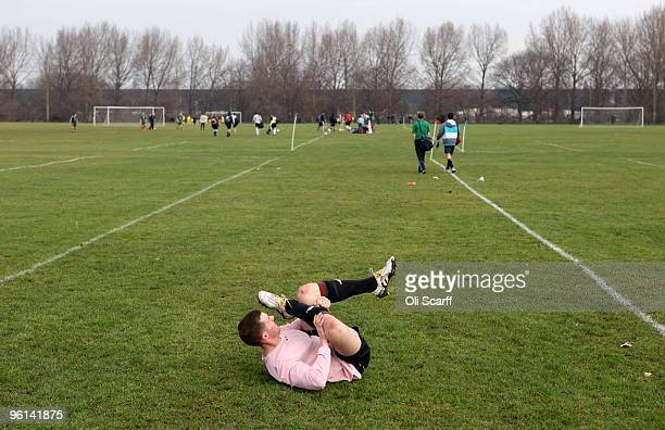 Sunday League footballer performs a leg stretch prior to playing on the Hackney Marshes on January 24 2010 in London England Hackney Marshes is known...