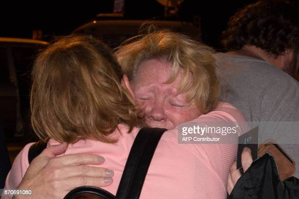 Sunday School director Ann Montgomery is comforted during a candlelight vigil held across the street from the First Baptist Church in Sutherland...