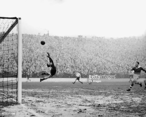Sunderland goalkeeper Willie Fraser springs into a curving leap to stop the ball as it flies to the net to give Charlton Athletic their second goal...