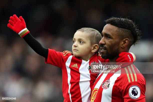Sunderland mascot Bradley Lowery waves to the crowd as Jermaine Defoe looks on ahead of during the Premier League match between Everton and...