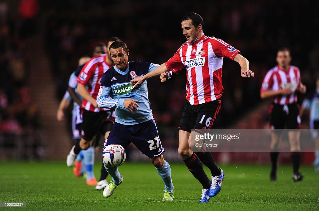 Sunderland player John O' Shea (r) battles for the ball with Scott Mcdonald of Boro during the Capital One Cup Fourth Round match between Sunderland and Middlesbrough at Stadium of Light on October 30, 2012 in Sunderland, England.