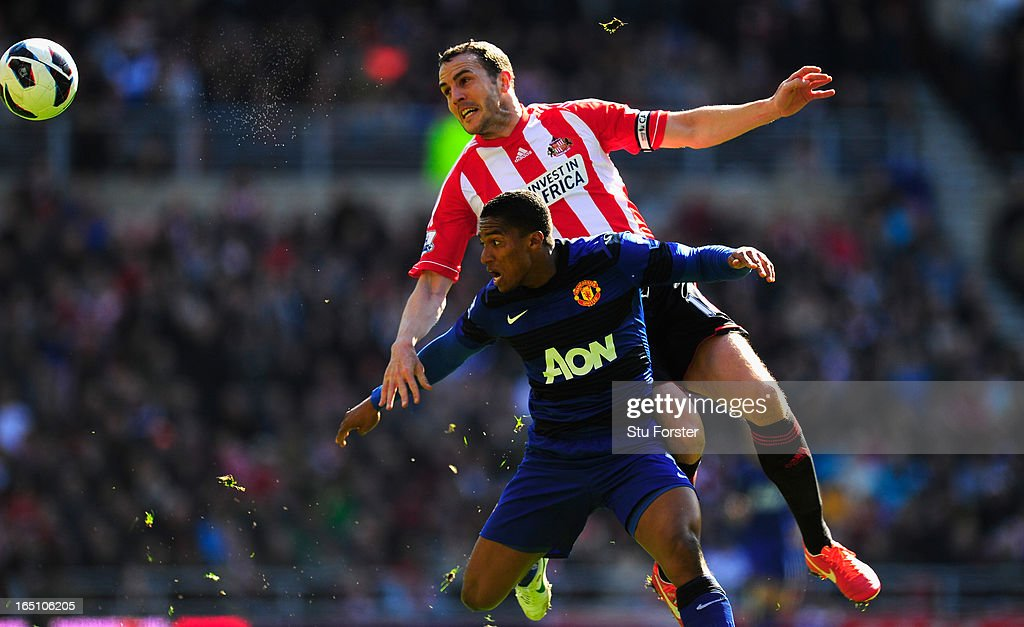 Sunderland player John O' Shea (r) challenges <a gi-track='captionPersonalityLinkClicked' href=/galleries/search?phrase=Antonio+Valencia&family=editorial&specificpeople=543830 ng-click='$event.stopPropagation()'>Antonio Valencia</a> during the Barclays Premier League match between Sunderland and Manchester United at Stadium of Light on March 30, 2013 in Sunderland, England.