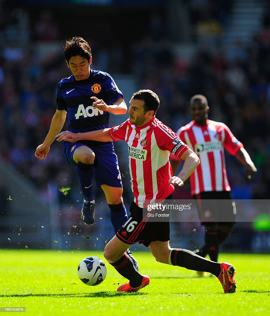 Sunderland player John O' Shea (R) challenges <a gi-track='captionPersonalityLinkClicked' href=/galleries/search?phrase=Shinji+Kagawa&family=editorial&specificpeople=4314029 ng-click='$event.stopPropagation()'>Shinji Kagawa</a> during the Barclays Premier League match between Sunderland and Manchester United at Stadium of Light on March 30, 2013 in Sunderland, England.