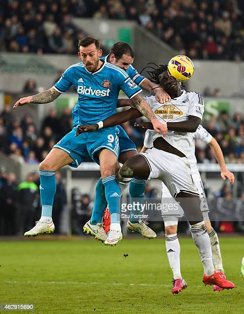 Sunderland players Steven Fletcher and John O' Shea challenge Bafetimbi Gomis of Swansea during the Barclays Premier League match between Swansea...