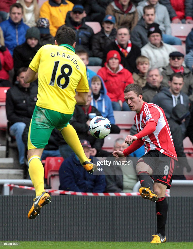 "Sunderland's Englisg midfielder Craig Gardner (R) shoots past Norwich's Spanish defender Javier Garrido (L) during the English Premier League football match between Sunderland and Norwich City at The Stadium of Light in Sunderland, north-east England, on March 17, 2013. The match ended 1-1. USE. No use with unauthorized audio, video, data, fixture lists, club/league logos or ""live"" services. Online in-match use limited to 45 images, no video emulation. No use in betting, games or single club/league/player publications."