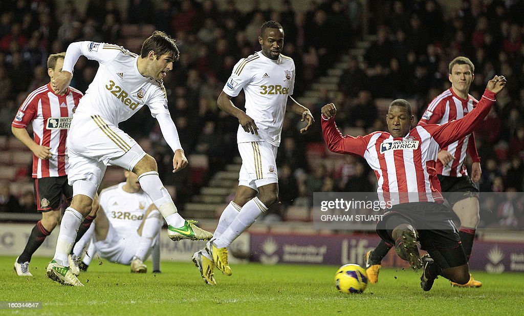 """Sunderland's English defender Titus Bramble (R) attempts to block a shot from Swansea City's English striker Danny Graham (L) during the English Premier League football match between Sunderland and Swansea City at The Stadium of Light in Sunderland, north-east England on January 29, 2013. The game finished 0-0. USE. No use with unauthorized audio, video, data, fixture lists, club/league logos or """"live"""" services. Online in-match use limited to 45 images, no video emulation. No use in betting, games or single club/league/player publications"""
