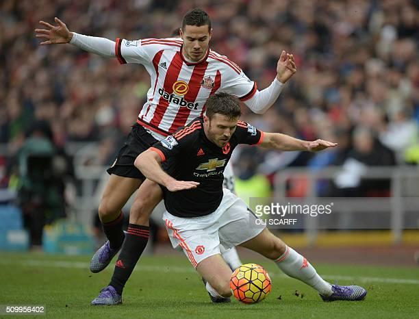Sunderland's English midfielder Jack Rodwell vies with Manchester United's English midfielder Michael Carrick during the English Premier League...