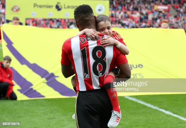 Sunderland's English striker Jermain Defoe holds Bradley Lowery a fiveyearold suffering from terminal cancer before the English Premier League...