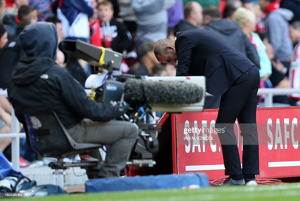Sunderland's Italian manager Paolo Di Canio (R) reacts after a disallowed goal during the English Premier League football match between Sunderland and Arsenal at the Stadium of Light in Sunderland, northeast England, on September 14, 2013. USE. No use with unauthorized audio, video, data, fixture lists, club/league logos or live services. Online in-match use limited to 45 images, no video emulation. No use in betting, games or single club/league/player publications.