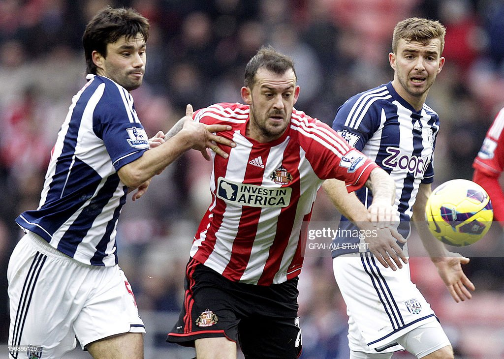 "Sunderland's Scottish striker Steven Fletcher (C) is challenged by West Bromwich Albion's Argentinian midfielder Claudio Yacob (L) during their English Premier League football match at the Stadium of Light in Sunderland, north-east England, on November 24, 2012. USE. No use with unauthorized audio, video, data, fixture lists, club/league logos or ""live"" services. Online in-match use limited to 45 images, no video emulation. No use in betting, games or single club/league/player publications"