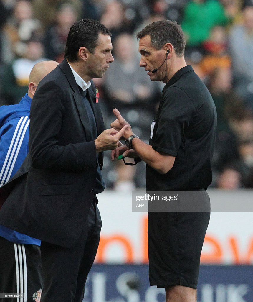 Sunderland's Uruguayan manager Gus Poyet (L) speaks to referee Andre Marriner during the English Premier League football match between Hull City and Sunderland at The KC Stadium in Hull on November 2, 2013. USE. No use with unauthorized audio, video, data, fixture lists, club/league logos or live services. Online in-match use limited to 45 images, no video emulation. No use in betting, games or single club/league/player publications.