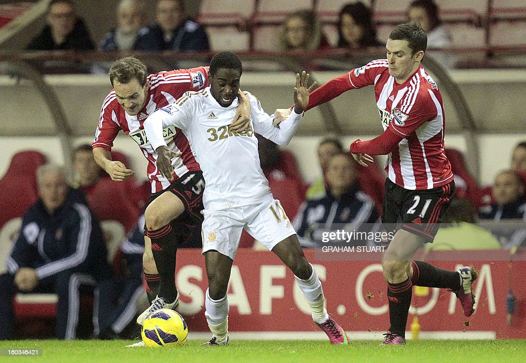 """Sunderland's Welsh midfielder David Vaughan (L) and English midfielder Adam Johnson (R) vie with Swansea City's English midfielder Nathan Dyer (2nd L) during the English Premier League football match between Sunderland and Swansea City at The Stadium of Light in Sunderland, north-east England on January 29, 2013. The game finished 0-0. USE. No use with unauthorized audio, video, data, fixture lists, club/league logos or """"live"""" services. Online in-match use limited to 45 images, no video emulation. No use in betting, games or single club/league/player publications"""