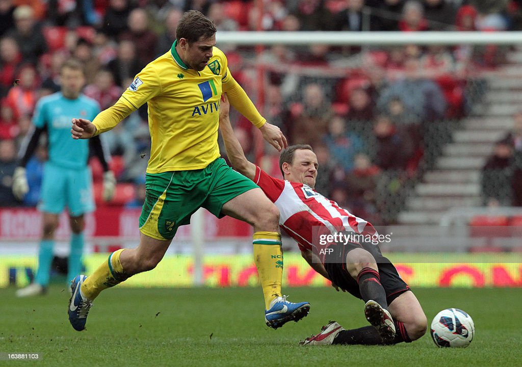 "Sunderland's Welsh midfielder David Vaughan (L) is tackled by Norwich's English forward Grant Holt during the English Premier League football match between Sunderland and Norwich City at The Stadium of Light in Sunderland, north-east England, on March 17, 2013. The match ended 1-1. USE. No use with unauthorized audio, video, data, fixture lists, club/league logos or ""live"" services. Online in-match use limited to 45 images, no video emulation. No use in betting, games or single club/league/player publications."