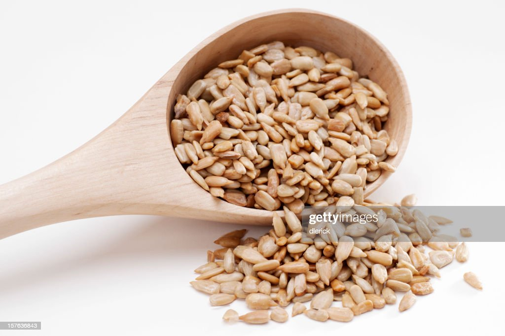 sunflower seed spilling from wooden spoon
