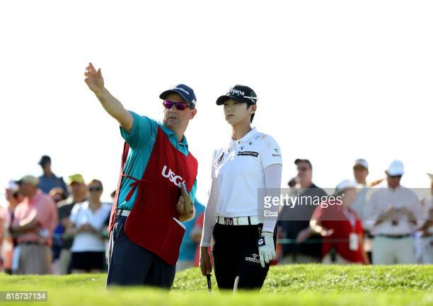 Sung Hyun Park of Korea and her caddie David Jones discuss her shot on the 16th tee during the final round of the US Women's Open on July 16 2017 at...