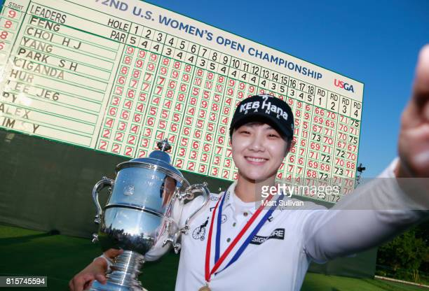 Sung Hyun Park of Sourth Korea imitates a 'selfie' with the championship trophy after winning the US Women's Open Championship at Trump National Golf...