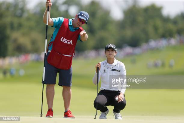 Sung Hyun Park of South Korea and her caddie David Jones line up a putt on the first hole during the final round of the US Women's Open Championship...