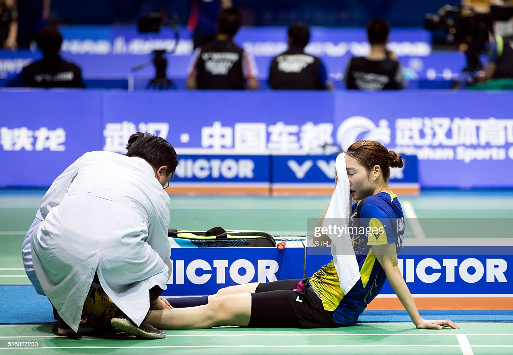 Sung Ji Hyun (R) of South Korea receives medical treatment during the women's singles quarter-final match against Sayaka Sato of Japan at the 2016 Badminton Asia Championships in Wuhan, central China's Hubei province on April 29, 2016. / AFP / STR