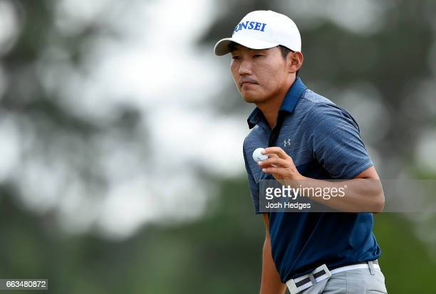Sung Kang of South Korea acknowledges the gallery after making a putt on the 12th green during round three of the Shell Houston Open at the Golf Club...