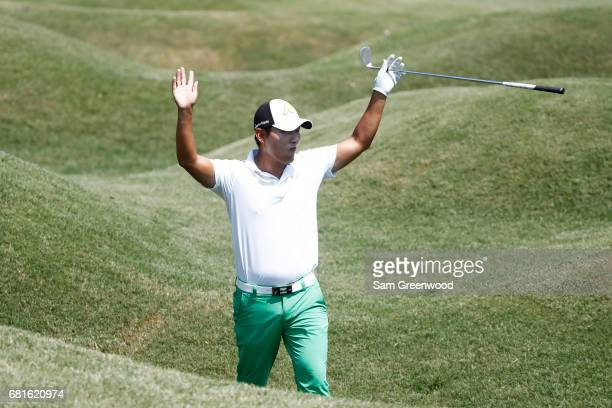 Sung Kang of South Korea reacts to chipping in during a practice round prior to THE PLAYERS Championship at the Stadium course at TPC Sawgrass on May...