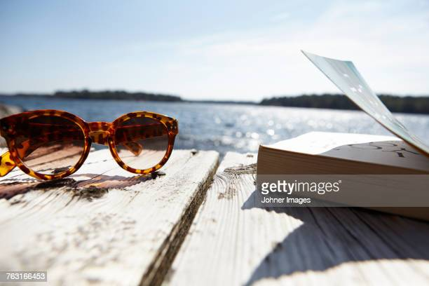 Sunglasses and book on wooden jetty, close-up