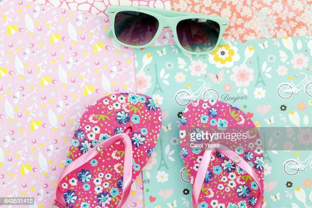 sunglasses and flip-flops on colourful background. Summer object.