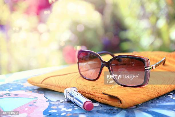 Sunglasses and lipstick on the table.