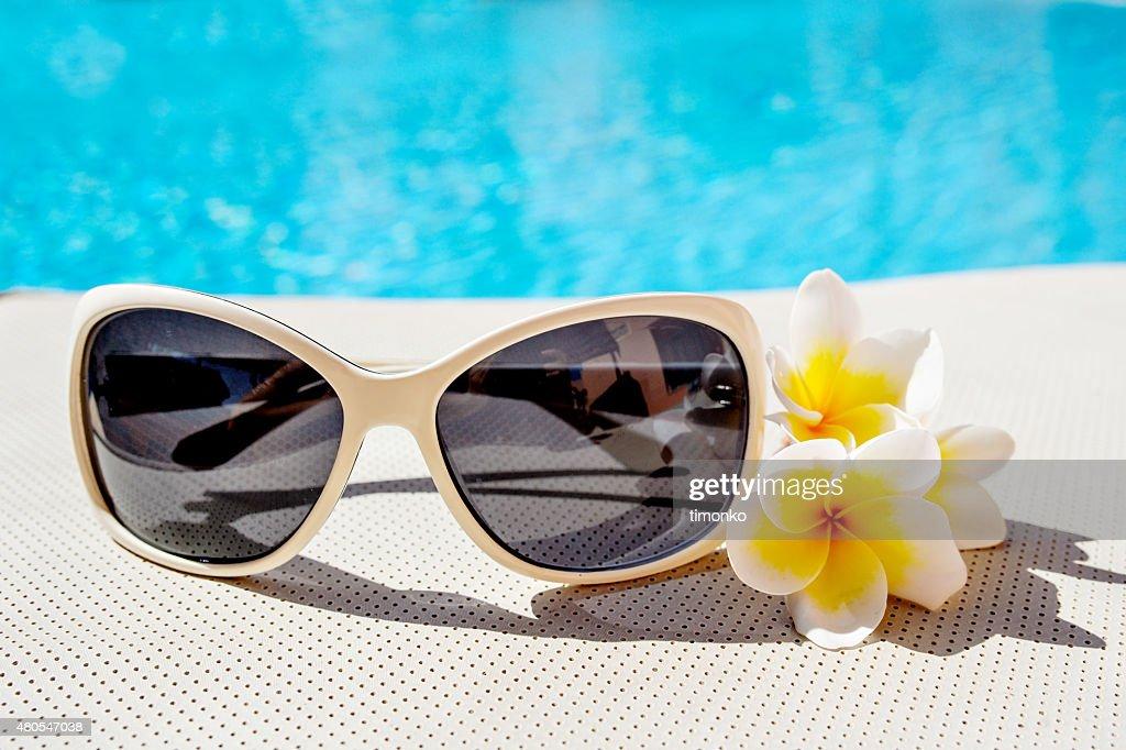 Gafas de sol y flores de plumeria cerca de la piscina : Foto de stock