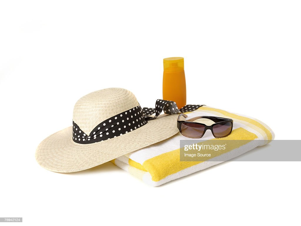 Sunglasses beach towel sunhat and suncream